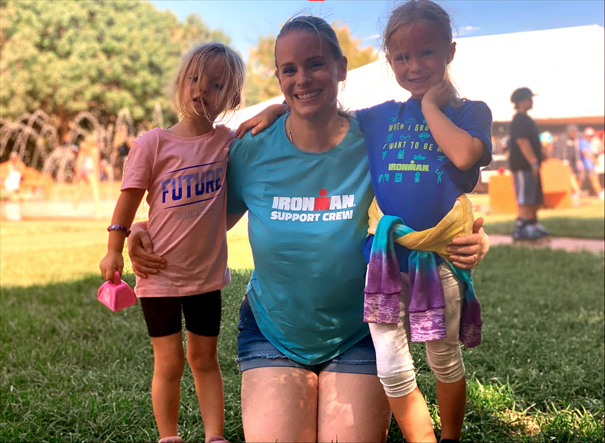 """a smiling white woman with blond hair kneels on the grass at a triathlon with her arms around her two young daughters on either side. Her blue tshirt says """"Ironman Support Crew."""" One daughter holds a pink bell in one hand and is wearing a pink tshirt that says """"Future Ironman"""" and the other daughter has a multicolored tie-dyed sweatshirt tied around her waist and is wearing a blue tshirt that says """"When i grow up i want to be an Ironman"""""""