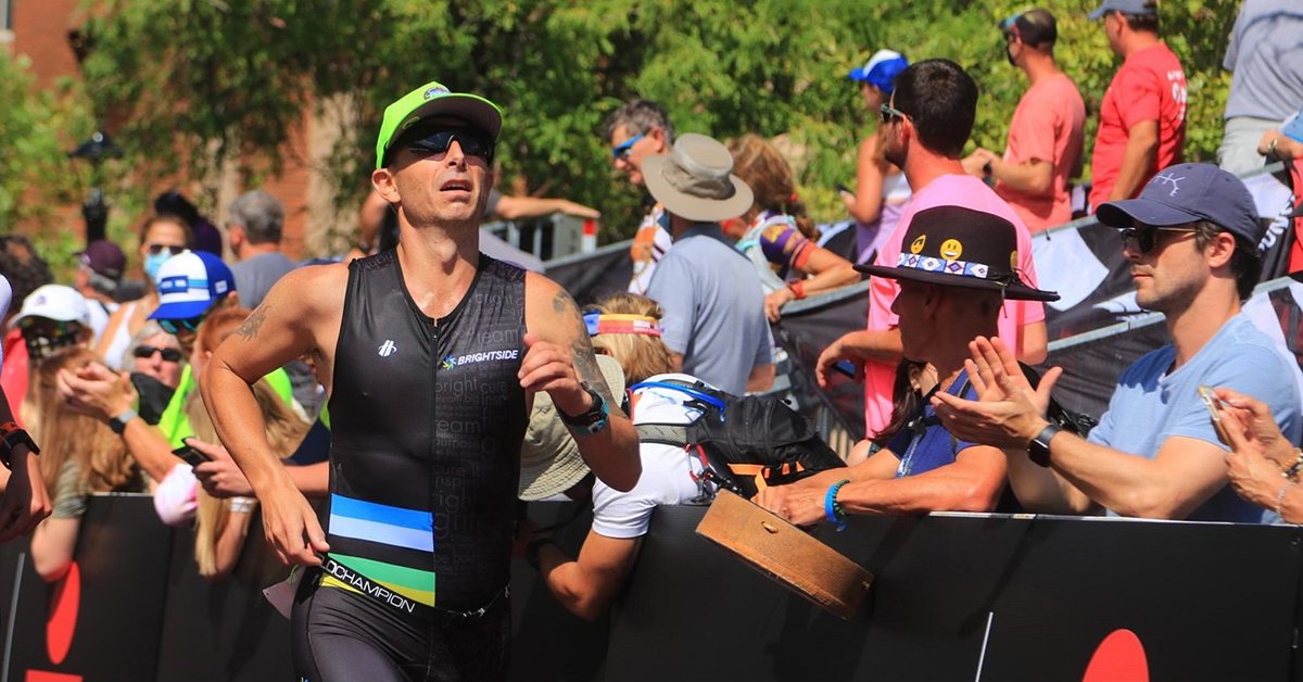 Brett Heyes, Credico's Director of National Accounts, competing in the 2021 Utah Ironman 70.3. He is seen running past an applauding crowd wearing a Team Bright Side tri kit, sunglasses, and a bright green cap.