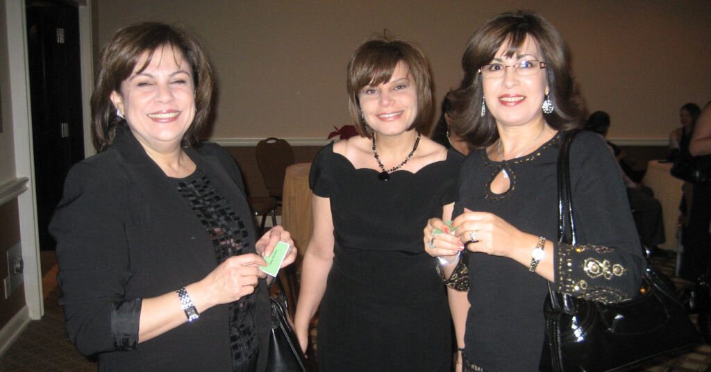 a group of three smiling women in black dresses at a Christmas party in 2008