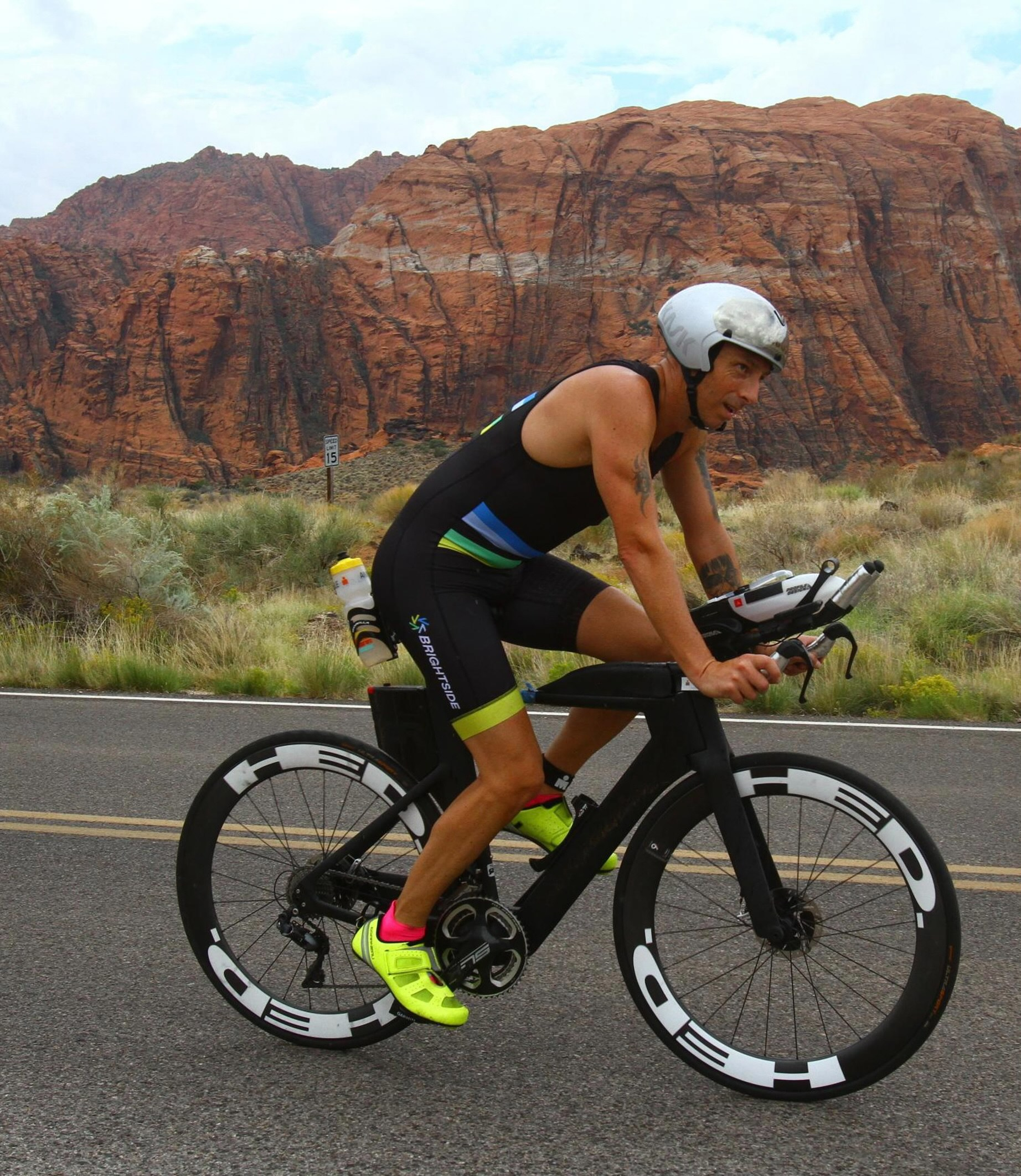 Brett Heyes, Credico's Director of National Accounts, rides past the red rocks of Utah. He is wearing a Team Bright Side tri kit, a silver helmet, and hi-viz yellow cycling shoes on a black bicycle with aero bars.