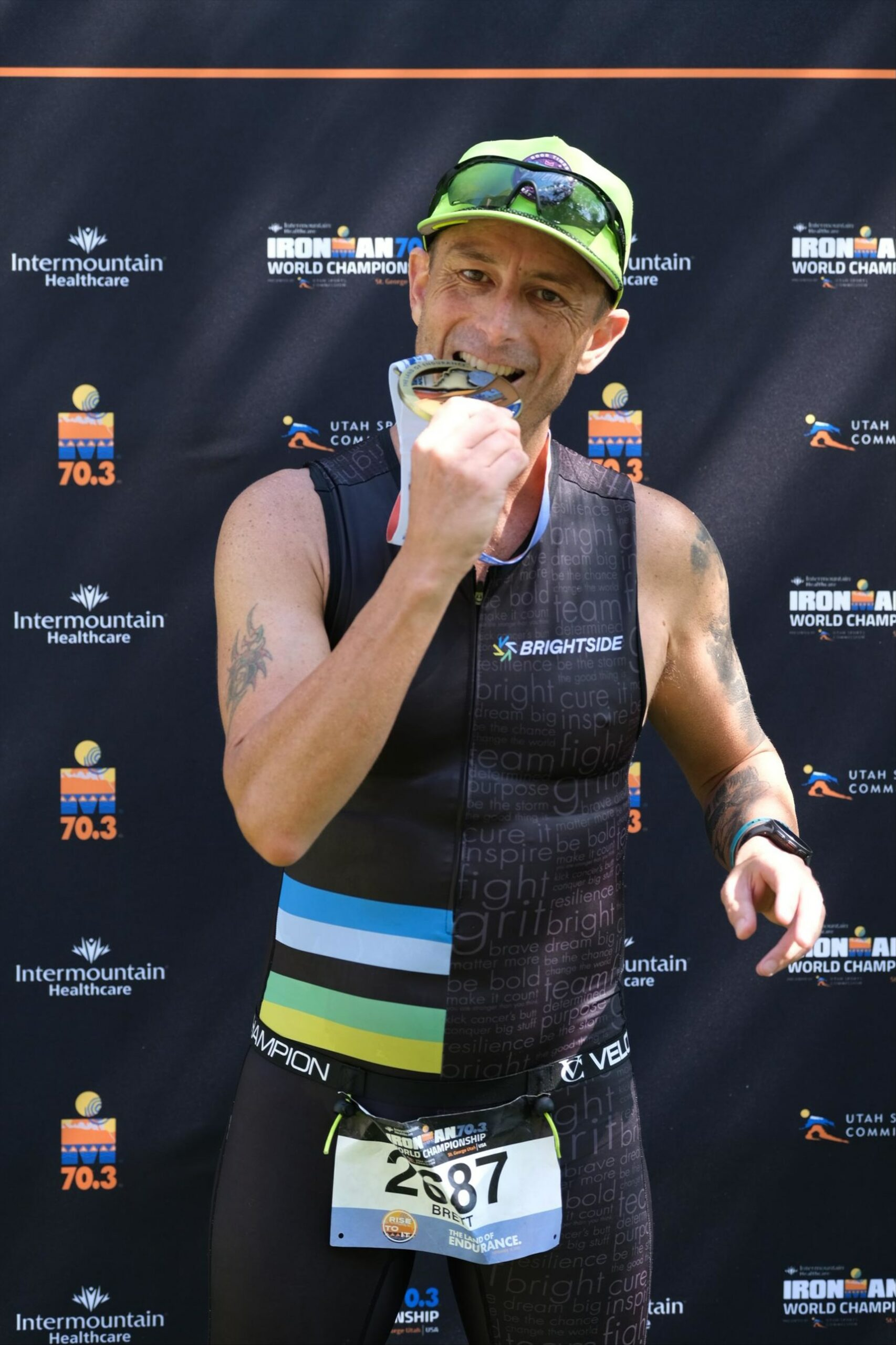 Brett Heyes, Credico's Director of National Accounts, bites his medal in front of an Ironman backdrop in his tri kit after completing a race.