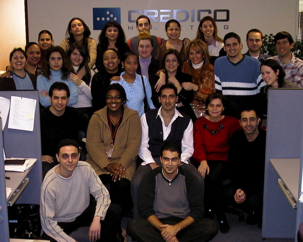 A group of people pose in a group at the end of a row of office cubicles in 2002