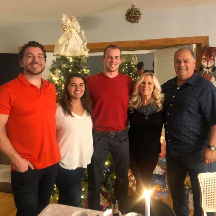 a family photo of Blake with his parents and siblings at home during Christmas